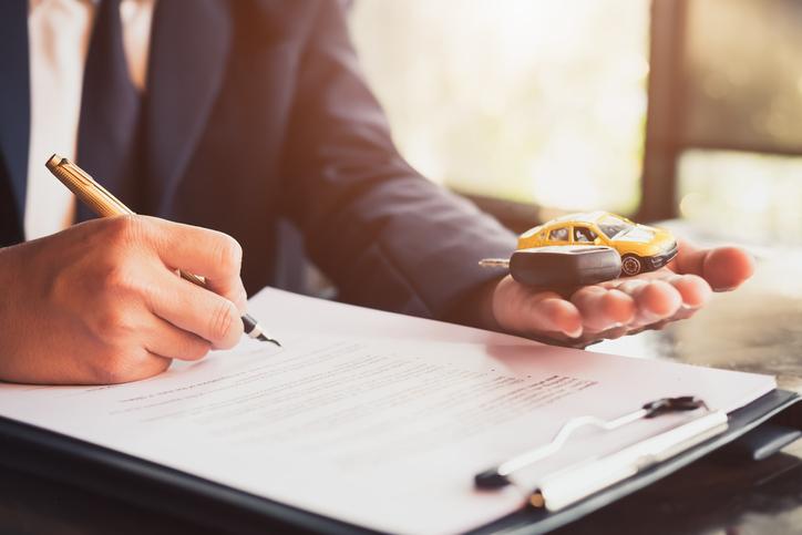 Homem de terno assina um contrato enquanto segura um carro em miniatura e uma chave na outra mão