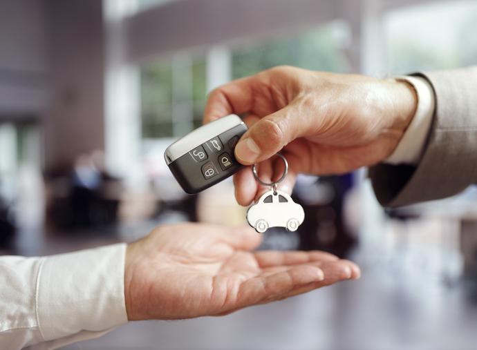 Imagem de uma mão masculina transferindo a chave de um carro para outra mão masculina