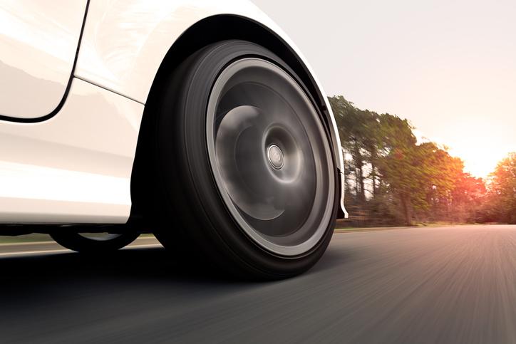 imagem mostra um carro branco, com foco no pneu dianteiro, em alta velocidade na estrada