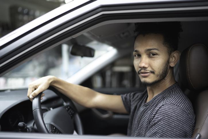 Jovem dirigindo carro e olhando para a foto